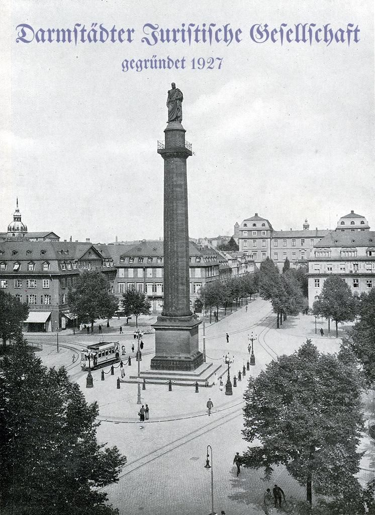 In der Mitte des Darmstädter Luisenplatzes steht die Ludwigssäulemit der Statue Ludwigs I., des Landgrafen und späteren Großherzogs. Auf dem Luisenplatz sind mehrere Personen und eine Straßenbahn zu sehen. Im Hintergrund befindet sich das Darmstädter Schloss.